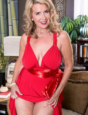 Mature blonde woman Laura Layne takes off her red dress to stand naked