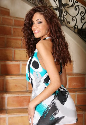Latina solo girl Isis Taylor plays with her curly hair in a black bikini