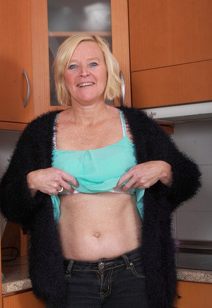 Mature housewife with blonde hair and blue eyes strips naked in her kitchen