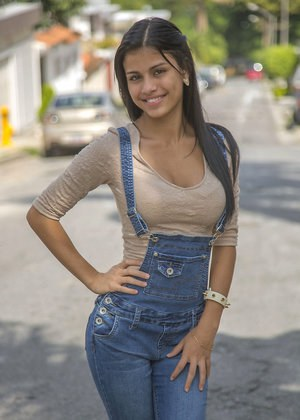 Clothed brunette teen Denisse Gomez shows off her pretty face in jean overalls