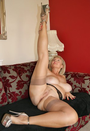 Mature lady with big tits drives a dildo up her snatch in nylons and garters
