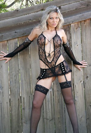 Blond lingerie model Ana Nova shows off her butt cheeks against a wooden fence