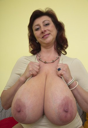 Mature woman in a miniskirt whips out her massive breasts on her sofa