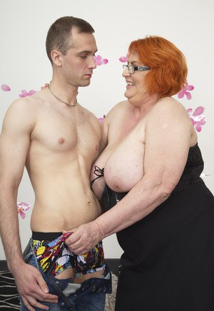 Redheaded BBW and her boy toy start to undress as they engage in foreplay