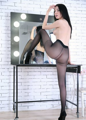 Dark haired solo model Amy Light removes pantyhose from her long legs