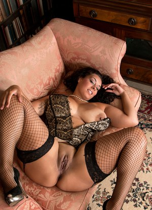 Overweight Latina in sexy lingerie and fishnet stockings baring large boobs