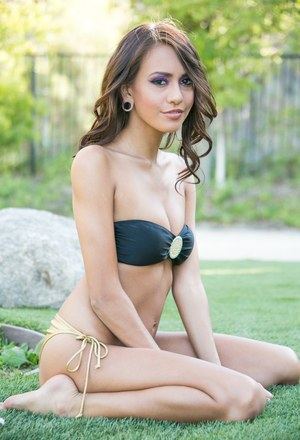 Latina female Janice Griffith poses in bikini before modeling naked on lawn
