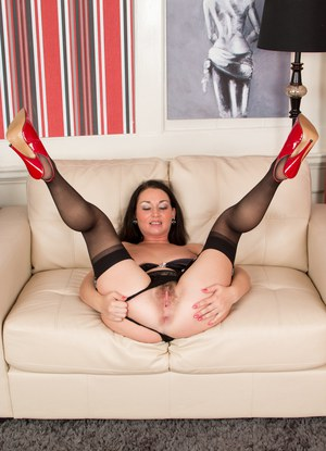 Brunette MILF in stockings and heels freeing hairy bush from lace underwear