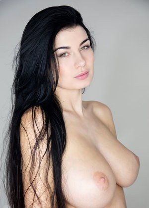 Dark haired beauty Lucy posing erotically in the nude to show her huge boobs