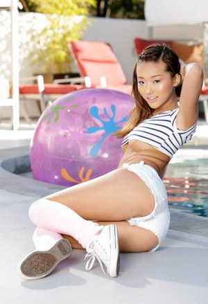 Cut Asian girl Alina Li strips to legs warmers and sneakers by a pool