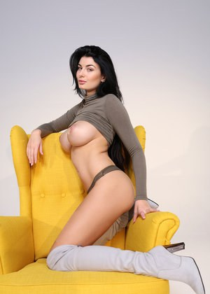 Dark haired solo model Lucy shows her stuff in over the knee boots