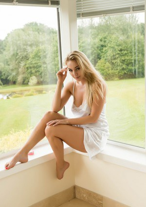 Sexy blonde female Hayley Marie Coppin undresses in a sunroom to pose nude