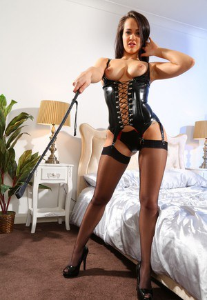 Brunette glamour model Felicity Hill poses in lace up lingerie with a crop