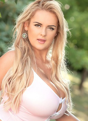Blonde solo girl Katie Thornton shows off her hooters in the garden area