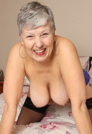 Thick grandmother from the UK squeezes her boobs together while disrobing