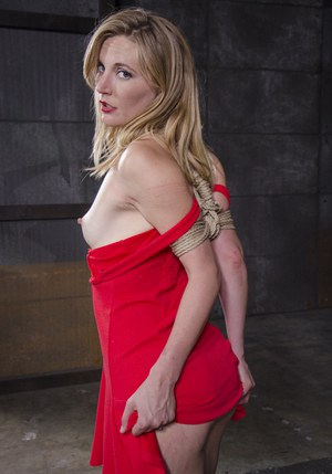 Blonde female Mona Wales has her first Shibari experience in a dungeon