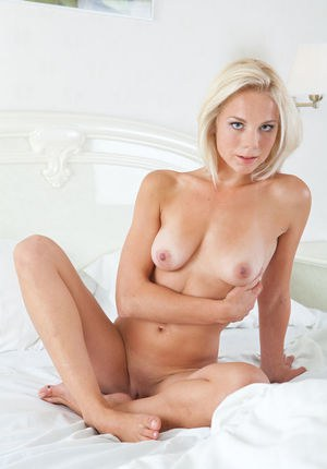 Blonde bombshell with sparkling blue eyes, Nena looks inviting as she's sprawled in bed wearing her matching white lingerie Latvia