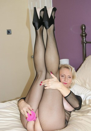 Hot mature woman dildos her landing strip pussy in crotchless bodystocking