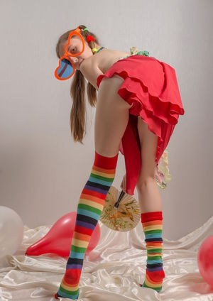 Skinny teen girl in pigtails and multi-colored socks takes off her clothes