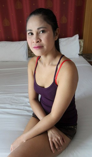 Thai solo girl hesitantly gets naked on a bed for a sex tourist