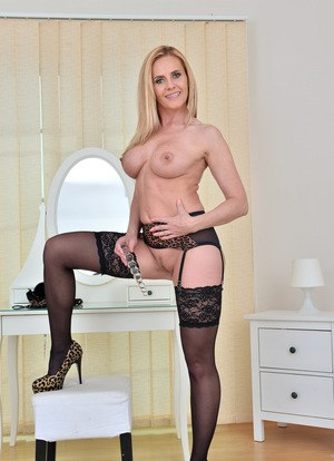 Big boobed mature blond slides a glass dildo up her pussy in hosiery and heels