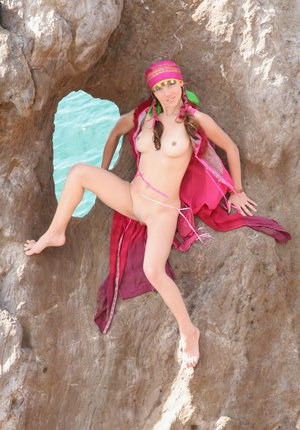 European teen Firebird A posing barefoot on rocky cliffs in revealing outfit