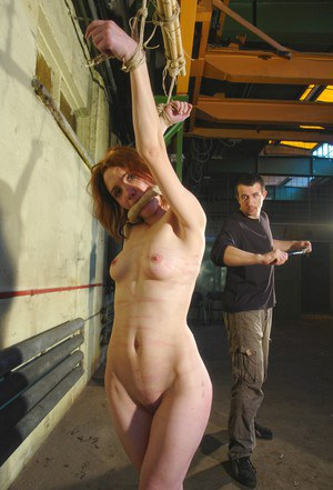 Naked redhead Lola is whipped and flogged while restrained in dungeon setting