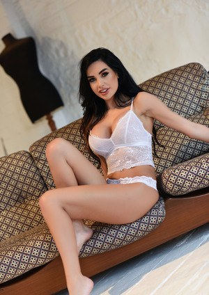 Dark haired Ann Denise in lace lingerie undressing to display big fake tits