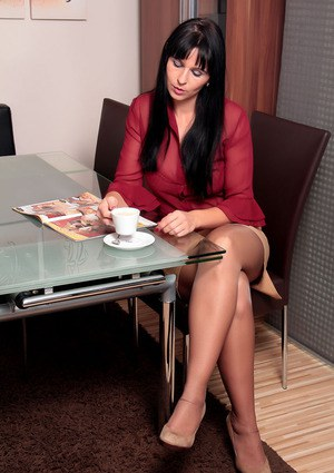 Busty brunette secretary gets naked in the office to spread stocking clad legs
