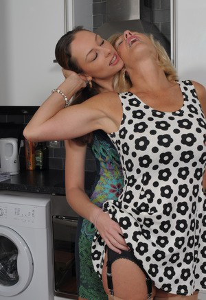 Younger woman and blonde granny lock lips for deep kiss in kitchen