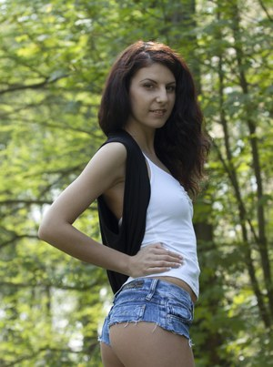 Skinny brunette girl cups a small tit as she undresses in nature