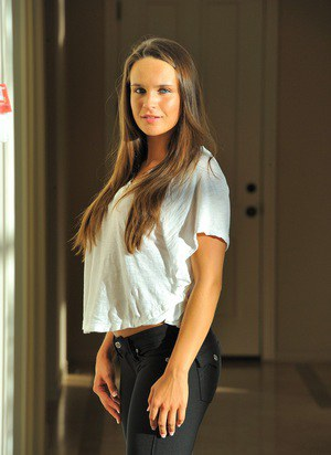 Teen solo girl with long hair uncovers her firm breasts in jeans