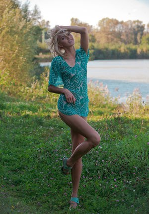 Sexy blonde teen Lilly A models naked in the grasses alongside a river