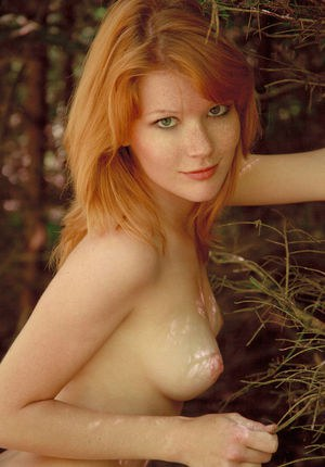 Nude redhead Mia Sollis flaunts her well formed body on cut line in forest