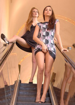 Inky lesbian girls lift their skirts for naked posing on a public escalator