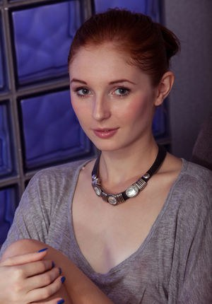 Pale redhead Leona Honey twists and turns her slim body to best show her pussy