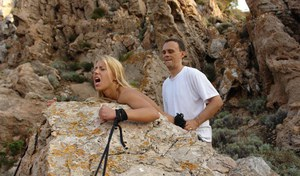 Blonde sex slave is led by a rope before getting fucked over a boulder