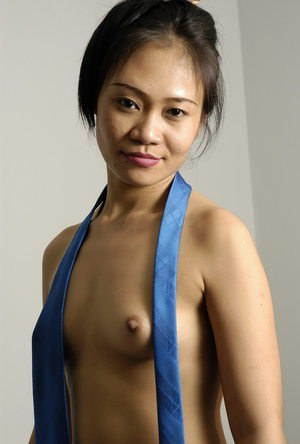 Attractive Asian girl showing her hard nipples wearing only a tie and boots