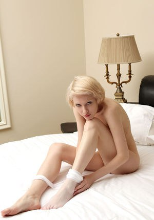 Erotic blonde Sindi pulls down her white pantyhose to bare her perfect pussy