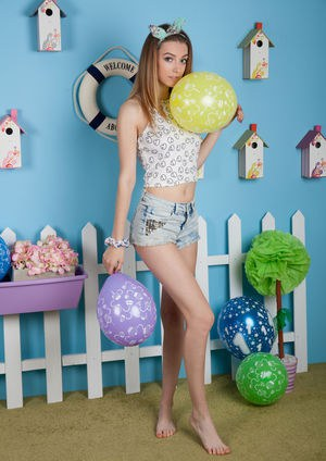 Innocent teen girl uncovers her big natural tits while posing with balloons