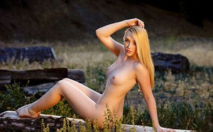 Beautiful blonde Samantha Rone casts aside her dress to pose naked in a field