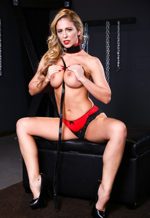 Blonde bombshell Cherie DeVille in collar & leash giving a blowjob in dungeon