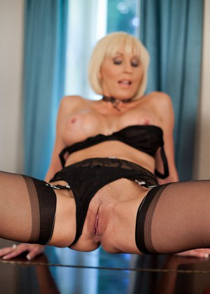 Blonde MILF in sexy black lingerie spreading wide in stockings on the piano