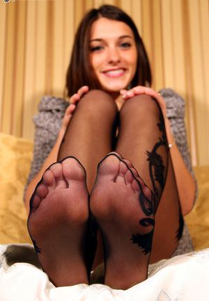 Sexy smiling brunette flaunts her sexy toes in black pantyhose