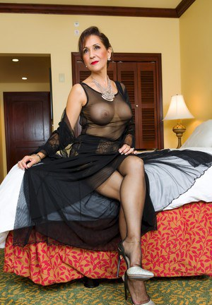 Classy older woman Roni Ford removes high heeled shoes from nylon attired feet