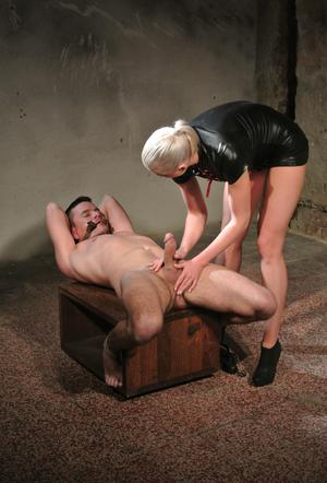 Mistress Victoria in latex treats her bound slave to a hot whipping  handjob