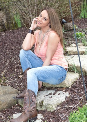 MILF Nikki Sims pulls down jeans to tease in cowgirl boots on stepping stones