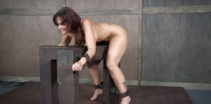Restrained woman Syren De Mer is used orally and vaginally in a dungeon