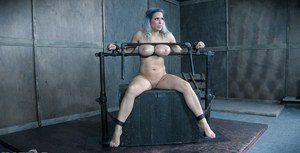 Naked female Alyssa Lynn has her large tits abused in bondage