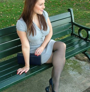 Clothed woman shows off her nylon ensconced legs and pumps in the park